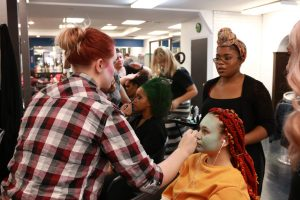 Students applying makeup to model dressed as Sally