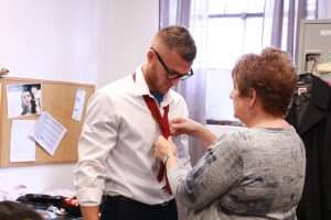 Academy of Hair Design educator helps model tie a red tie