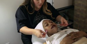 Esthetics student performing facial on young woman
